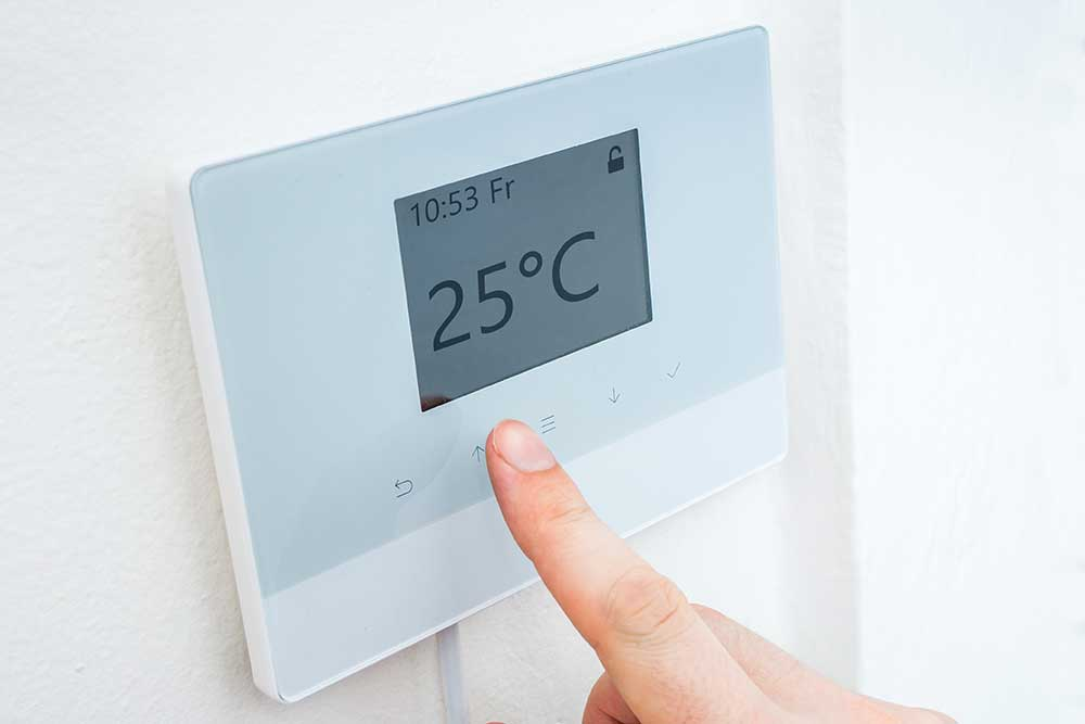 person touching wall mounted heating control